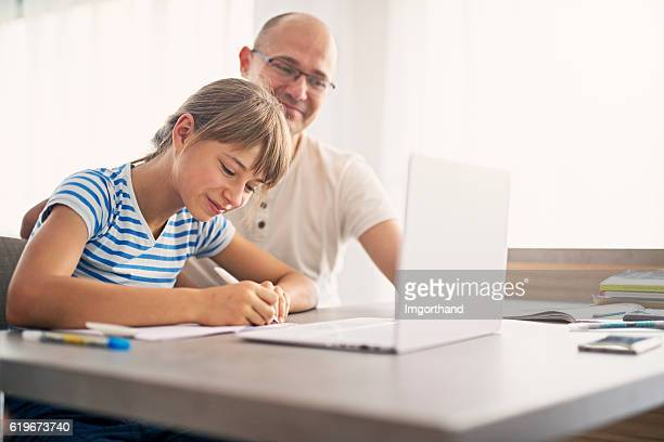 father doing homework with his daughter - homeschool ストックフォトと画像