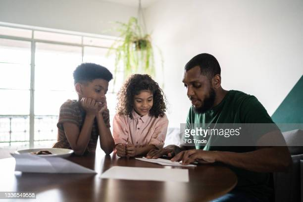 father doing paper airplane and teaching siblings at home - affectionate stock pictures, royalty-free photos & images