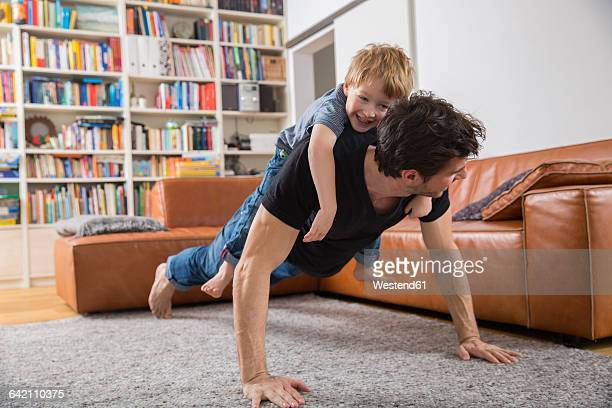 father doing push ups in living room with son on his back - piggyback stock pictures, royalty-free photos & images