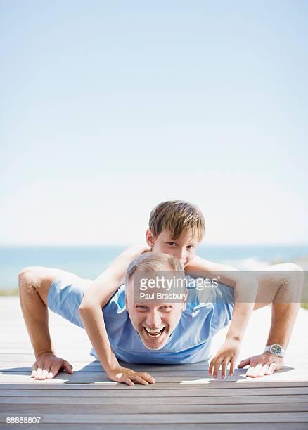 Pai fazendo push-up com a filha nas costas