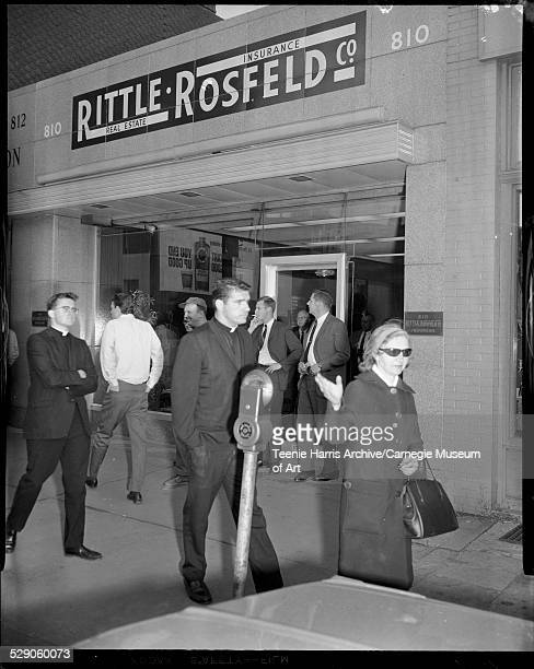 Father Donald McIlvane Father O'Malley and group of men and women protesting on sidewalk in front of Rittle Rosfeld Insurance and Real Estate Company...