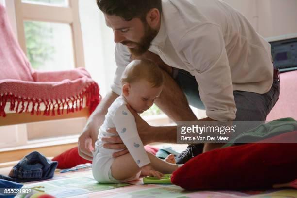 father dresses baby son at home. - padre amo de casa fotografías e imágenes de stock
