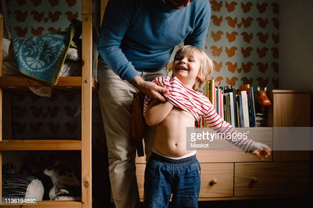 father dressing cheerful daughter at home - getting dressed stock pictures, royalty-free photos & images