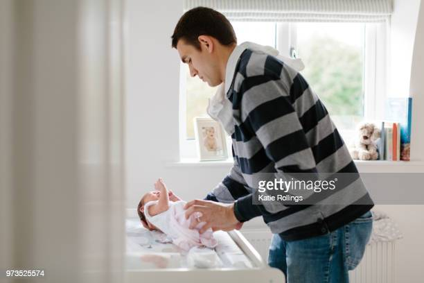 father dressing newborn baby - cobham surrey stock pictures, royalty-free photos & images