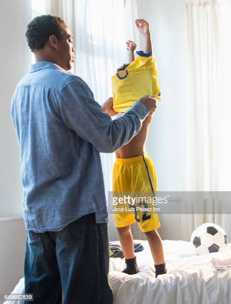 Father dressing son in soccer uniform