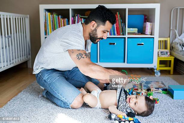 Father dressing up baby girl on carpet in bedroom