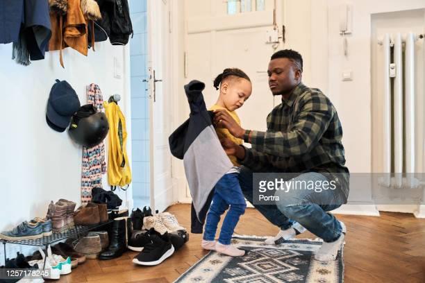 vader die zoon in woonkamer kleedt - jak jas stockfoto's en -beelden