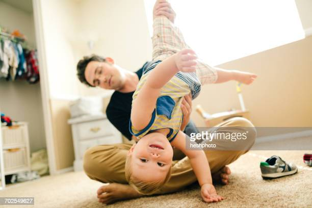 father dressing young son, father holding son upside down - heshphoto stock pictures, royalty-free photos & images