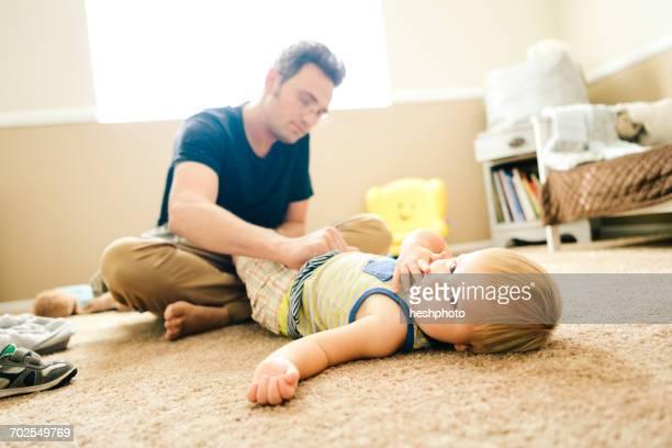 father dressing young son - heshphoto stock-fotos und bilder