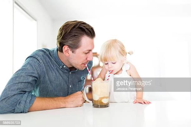 Father drinking milkshake with daughter (2-3)
