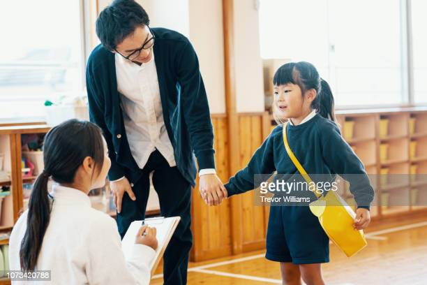 father dropping off young daughter at preschool - preschool building stock pictures, royalty-free photos & images