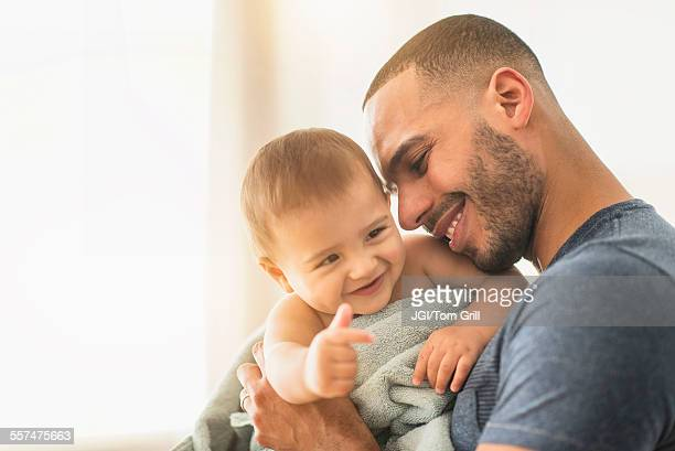 Father drying baby son with towel after bath