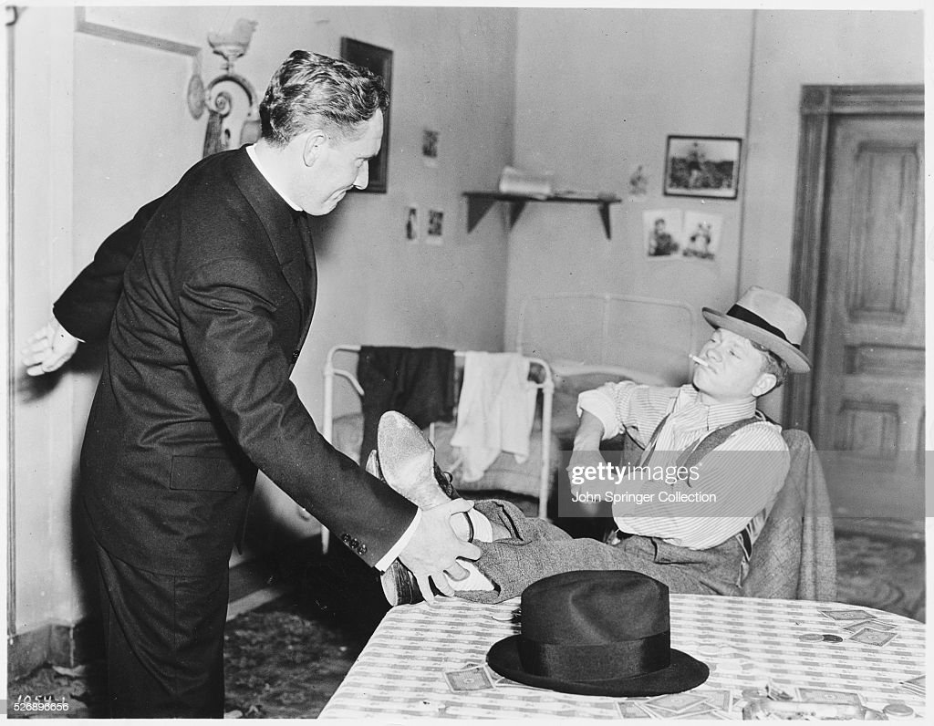 father edward flanagan pushes whitey marsh s feet off of a table in