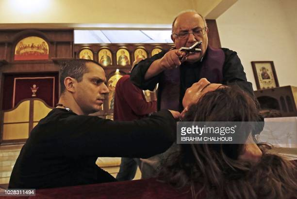 Father Elias Rahal performs exorcism ritual on a Lebanese lady at a church in the district of Mina in the northern port city of Tripoli on April 19...