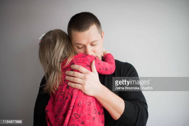 Father Embracing Daughter Against Gray Background