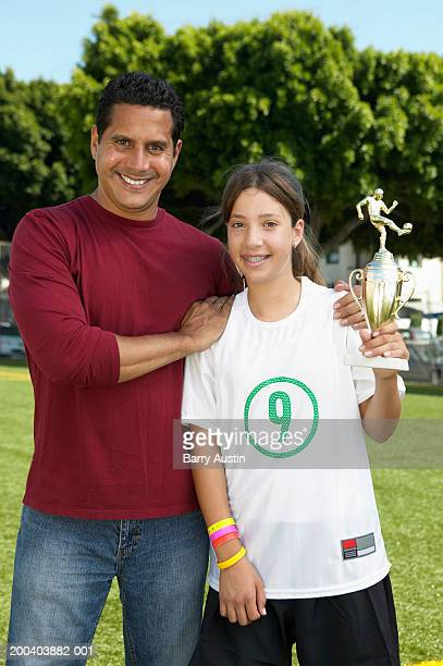 Father embracing daughter (11-13) holding football trophy, portrait