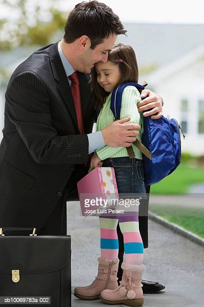 father embracing daughter (4-5) on street - genderblend stock-fotos und bilder