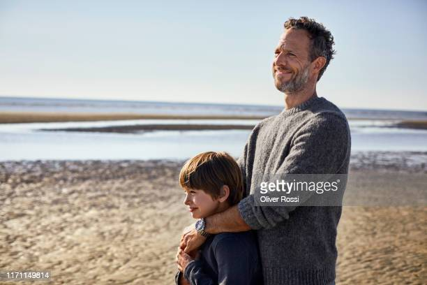 father embracing son on the beach - sohn stock-fotos und bilder