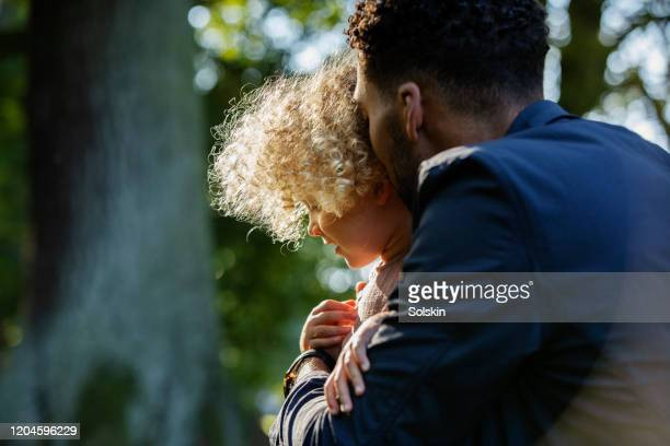 father embracing young daughter in park area - one parent stock pictures, royalty-free photos & images