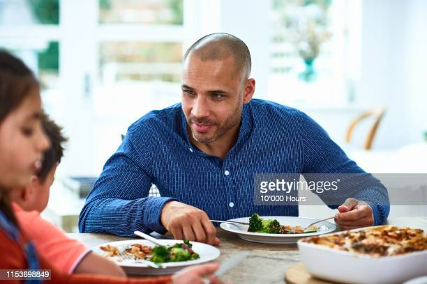 father encouraging children to eat healthy meal - filipino family dinner stock pictures, royalty-free photos & images