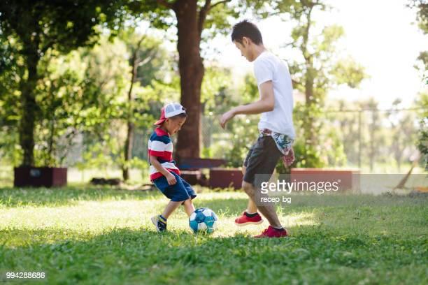 父が彼の子供たちとサッカーを楽しんで - 余暇 ストックフォトと画像