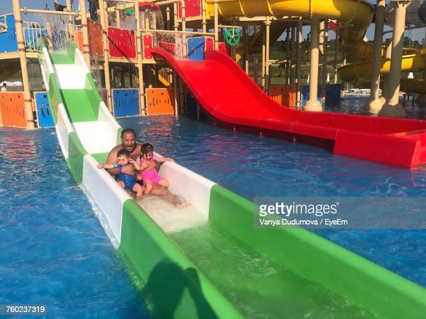 Father Enjoying With Children On Water Slide At Park