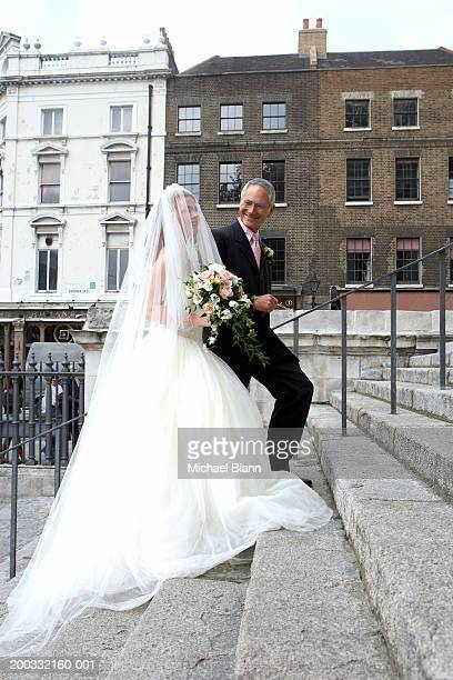 Father escorting bride up steps to church, smiling