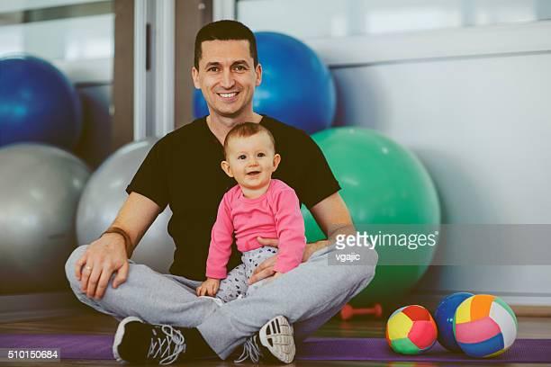 Père exercice avec son bébé dans une salle de sport.