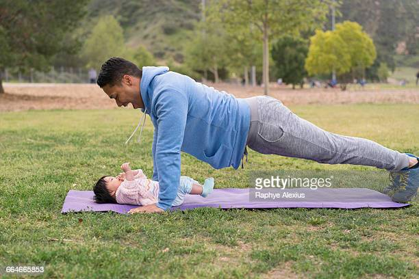 Father exercising with baby in park