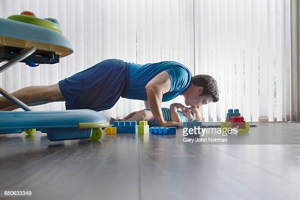 Father exercising with baby on floor