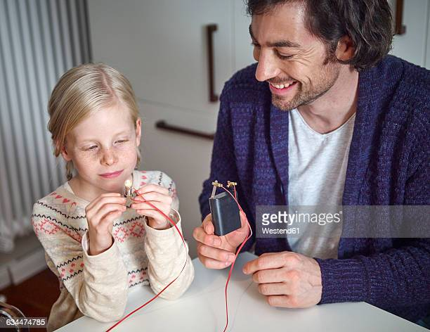 Father explaining circuit to daughter with battery and buld