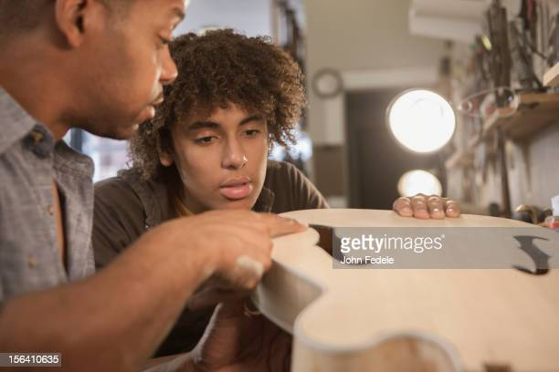 Father explaining guitar construction to son