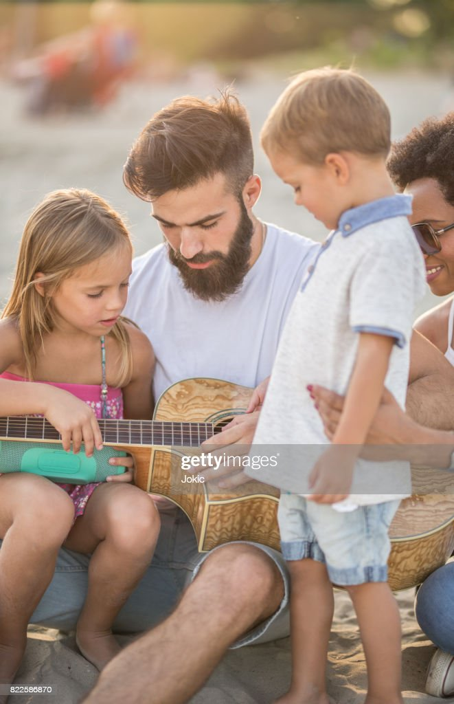 Father explains to children how to play a guitar. : Stock Photo