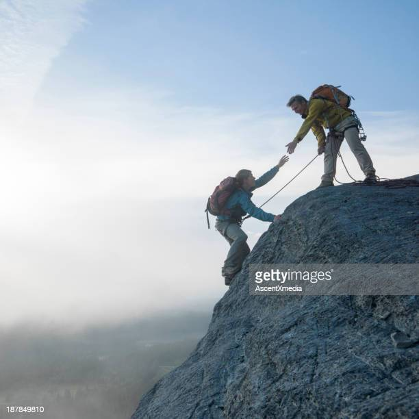 Father extends helping hand to son, while climbing