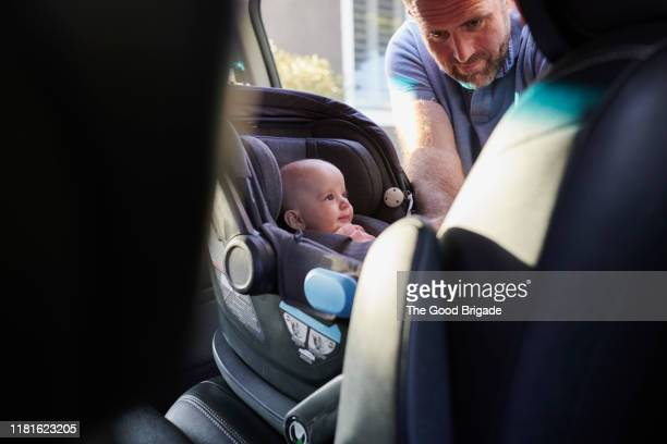 father fastening baby girl into car safety seat - lgbtq  and female domestic life fotografías e imágenes de stock