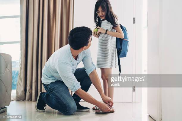 father fastening his daughter's shoes at the doorway - school girl shoes stock pictures, royalty-free photos & images