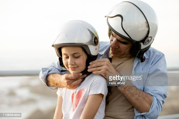 Father fastens daughter's motorcycle helmet