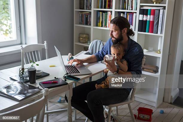 father feeding baby boy while using laptop at home - home icon stock photos and pictures