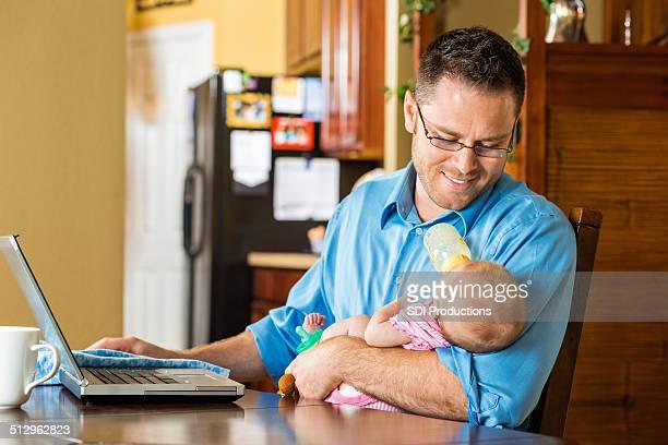 父と娘フィーディング赤ちゃん仕事のノートパソコンをご自宅で