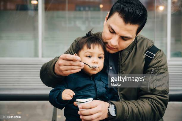 father feeding baby food to son while sitting on bench in city - paternity leave stock pictures, royalty-free photos & images