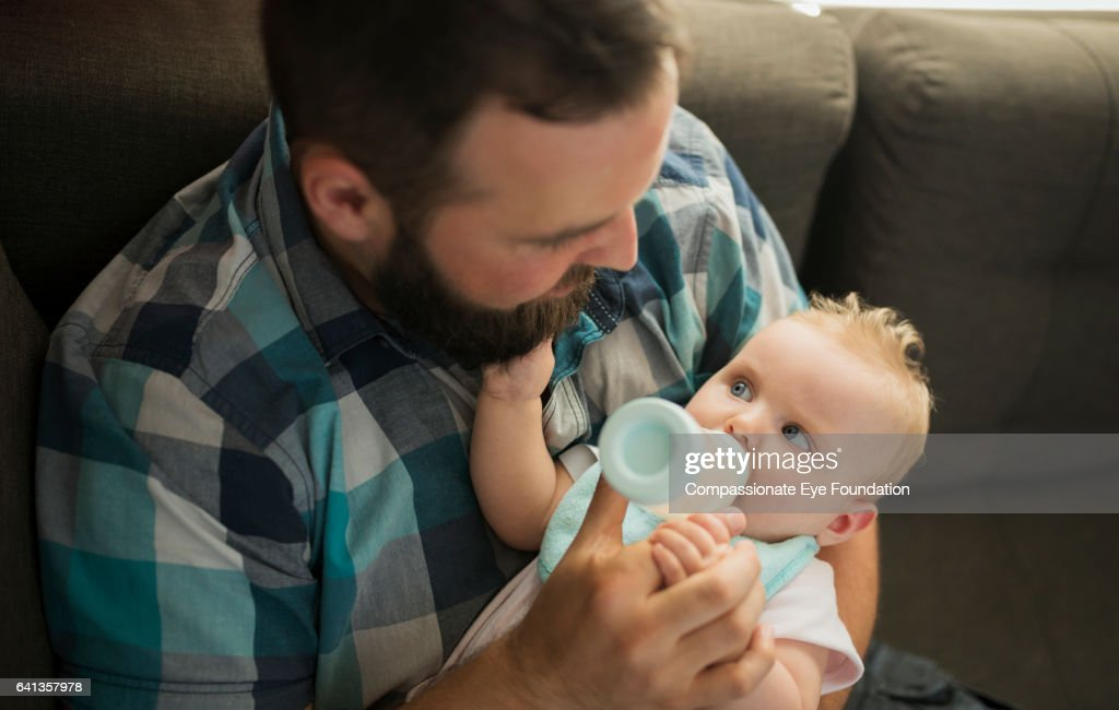 Father feeding baby girl from bottle : Stock Photo