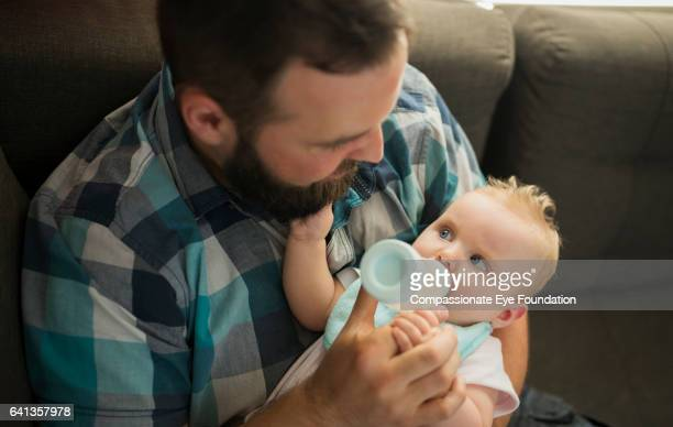 father feeding baby girl from bottle - photography stock pictures, royalty-free photos & images