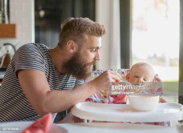 father feeding baby girl (12-23 months) on high chair - feeding stock pictures, royalty-free photos & images