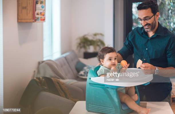 Father feeding baby girl.