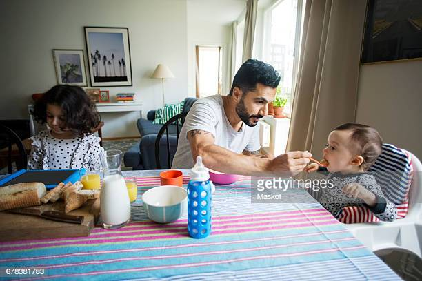 Father feeding baby girl while sitting by daughter using digital tablet at table