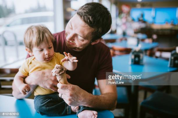 father feeding baby ice cream cone - ice cream parlour stock pictures, royalty-free photos & images