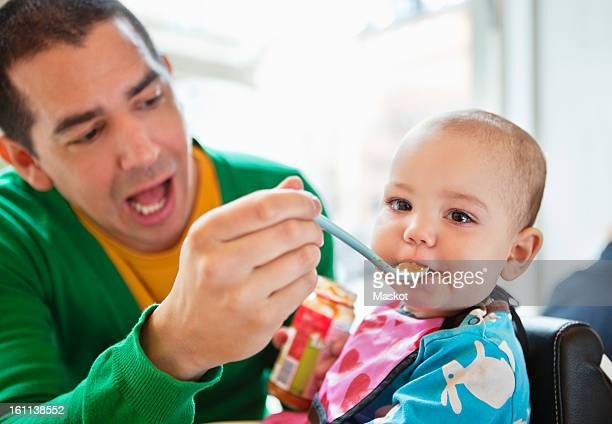 Father feeding baby with plastic spoon