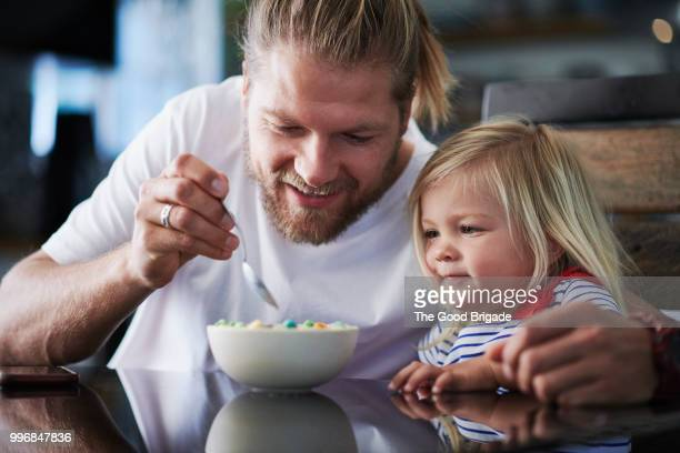 Father Feeding Breakfast To Cute Little Girl At Table