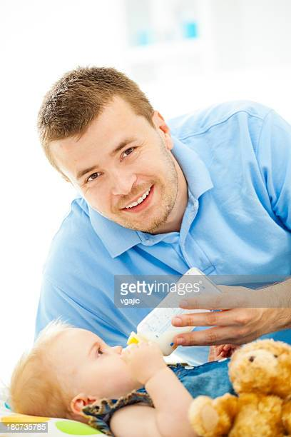 Father feeding child with baby bottle.