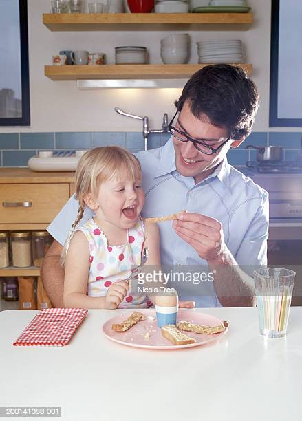Father feeding daughter (3-5) at table